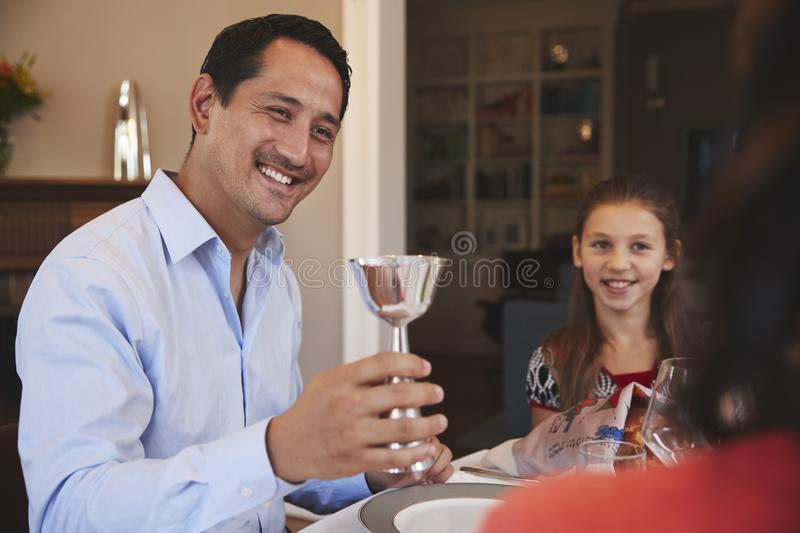 Jewish man holding kiddish cup blesses family at Shabbat royalty free stock image