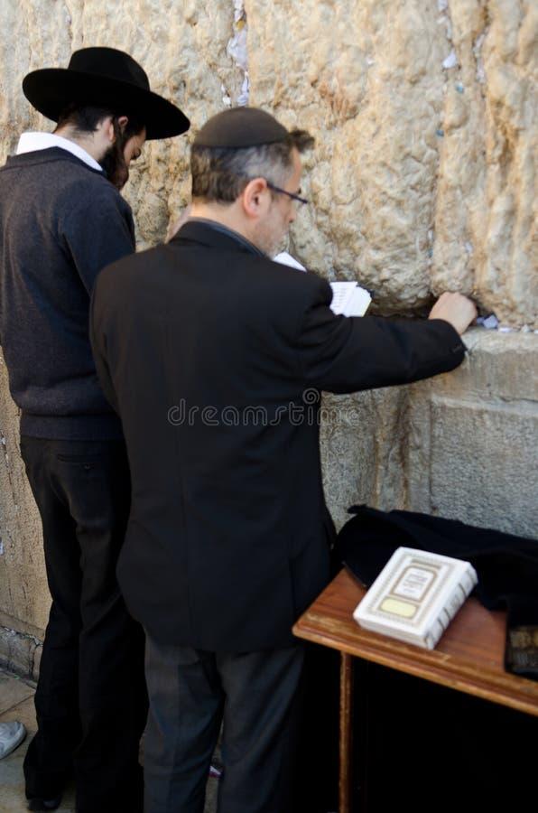 Jewish men praying at the Western wall stock photos