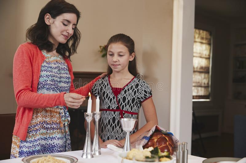 Jewish mother and daughter lighting candles for Shabbat meal stock photography