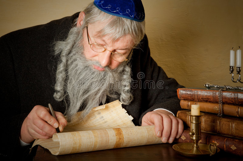 Jewish parchment. Old jewish man with beard writing on a parchment scroll royalty free stock photo