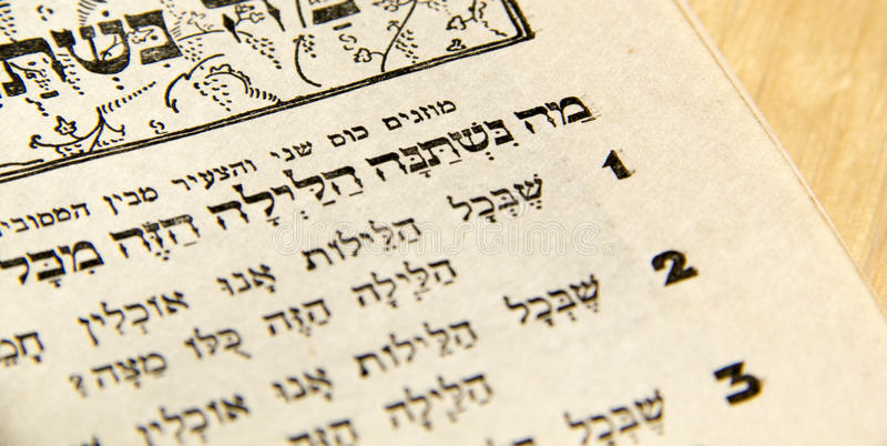 Jewish Passover haggadah fragment. Closeup of Hebrew text in traditional vintage Passover haggadah What makes this night different from all [other] nights? stock photo