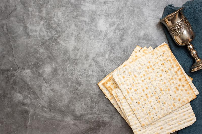 Jewish Passover holiday. Matza and glass for wine on a grey background. Top view. With copy space royalty free stock photography