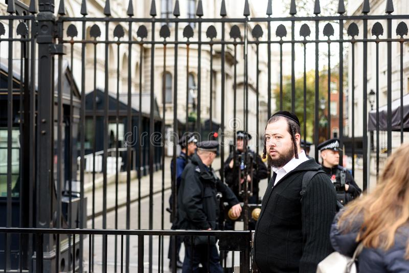 Jewish Tourist 10 Downing Street. Jewish tourist poses outside of 10 Downing Street with armed police ARU units in the background stock image