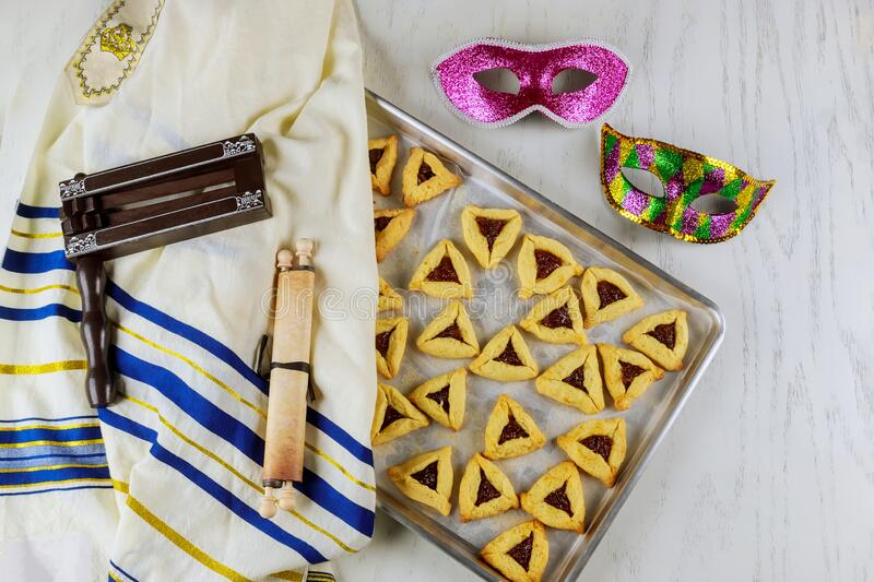 Jewish triangle cookies for Purim with tallit, tora and noisemaker stock photography