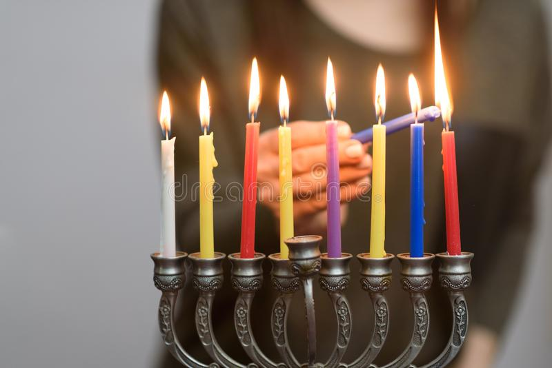 Jewish Woman lighting Hanukkah Candles in a menorah. People celebrate Chanukah by lighting candles on a menorah, also called a Hanukiyah. Each night, one more stock photos