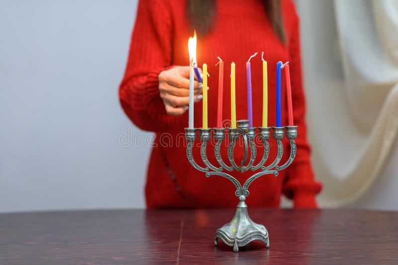 Jewish Woman lighting Hanukkah Candles in a menorah. People celebrate Chanukah by lighting candles on a menorah, also called a Hanukiyah. Each night, one more stock image