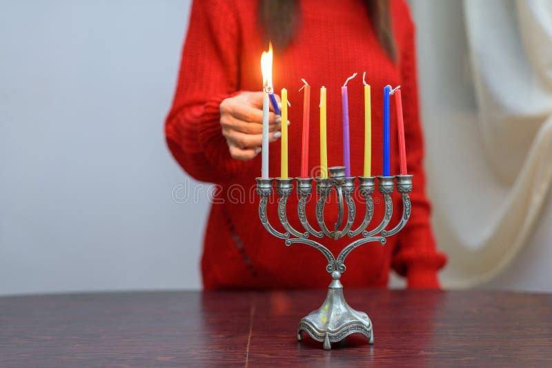 Jewish Woman lighting Hanukkah Candles in a menorah. stock image