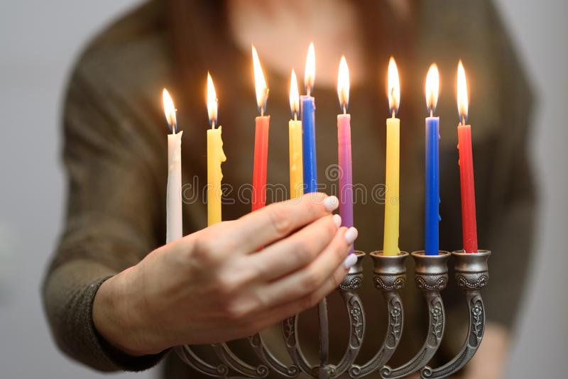 Jewish Woman lighting Hanukkah Candles in a menorah. People celebrate Chanukah by lighting candles on a menorah, also called a Hanukiyah. Each night, one more royalty free stock photo