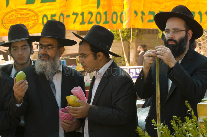 Jews preparing for succoth. During Succoth a person does not fulfill his obligation until all four varieties are in his hand. Orthodox jews will spend large royalty free stock images