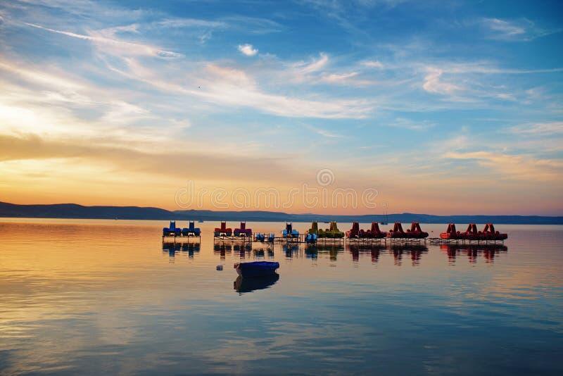 Jeziorny Balaton przy zmierzchem z pedalos i następ łodziami przy Balaontlelle, Węgry fotografia royalty free