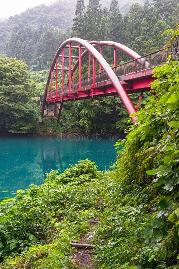 Jeziorny brzeg z ścieżką i czerwieni zawieszenia mostem obrazy stock