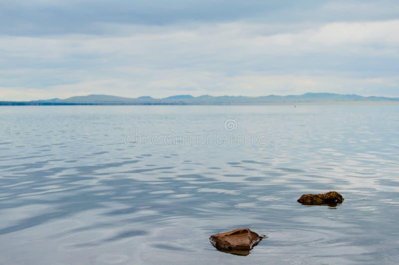 Jezioro i rzeka w przodzie z niektóre górami w tle Niektóre kamienie na linii frontu zdjęcie stock