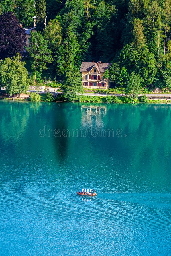 Jezioro Krwawiący, Slovenia, - Tradycyjna Słoweńska Pletna łódź na jeziorze Krwawiącym z turkusową błękitne wody, weekendu domem  fotografia stock