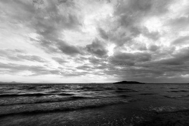 Jezioro przy półmrokiem, z majestatycznym cloudscape, zmrok wodą i wyspą w tle, fotografia royalty free