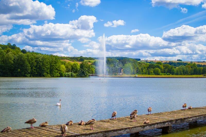 Jezioro w ?rodku park z dokiem i mn?stwo kaczki przy przedpolem, fontanna, drzewa i g?ry przy t?em, fotografia royalty free