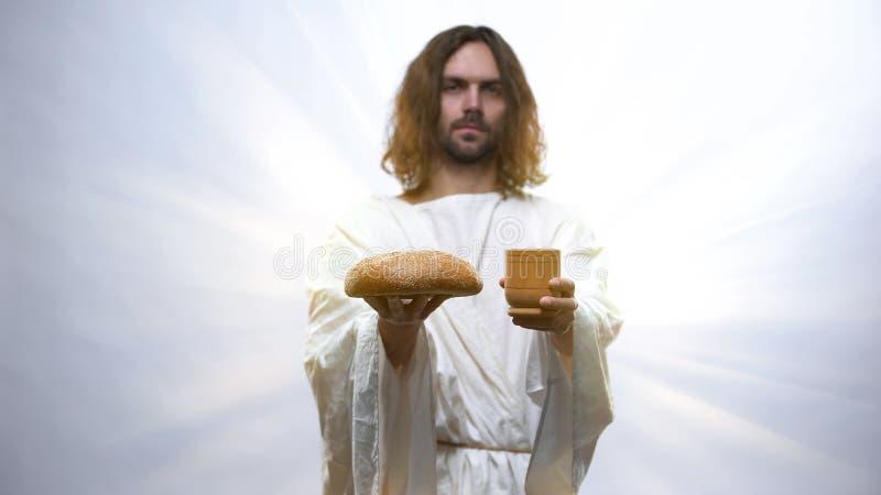 Jezus houdt wijn en brood op een verlichte achtergrond, christelijke ceremonie stock fotografie