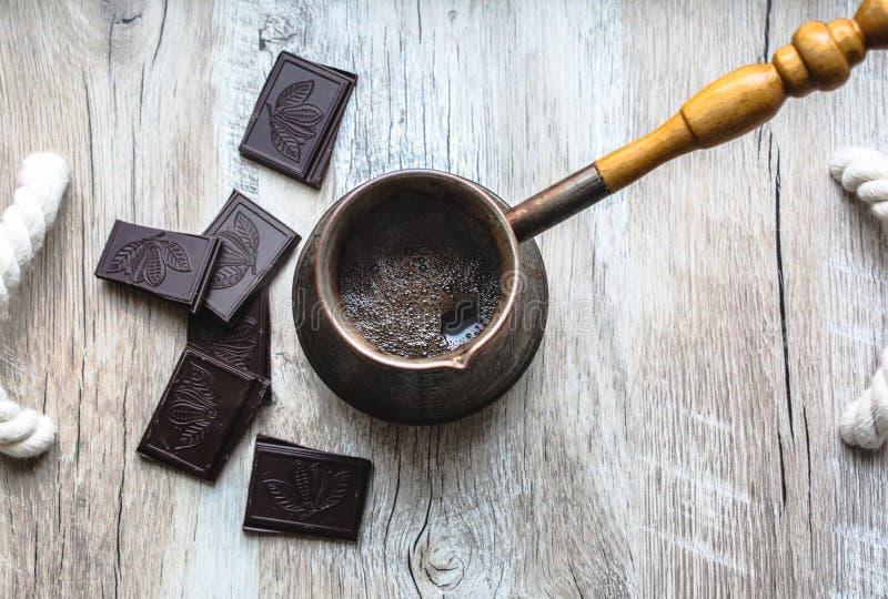 Jezve del vintage con café recientemente preparado El chocolate negro con las habas del cacao canta en la bandeja de madera con l fotos de archivo libres de regalías
