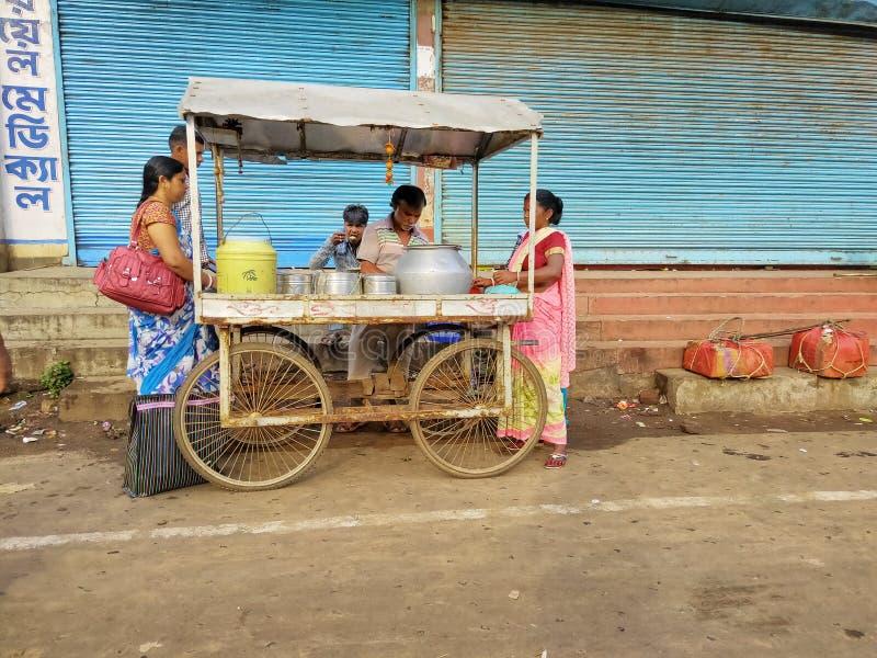 Jhargram, Bengal ocidental, Índia - 5 de maio de 2018: um vendedor de alimento da rua vendia o edli, uma cabeceira indiana sul do fotos de stock