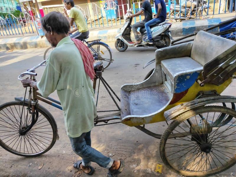 Jhargram, Bengala Occidental, la India - 5 de mayo de 2019: Un rickshwa tirado mano fue tirado por alguien en un camino ocupado d fotos de archivo libres de regalías