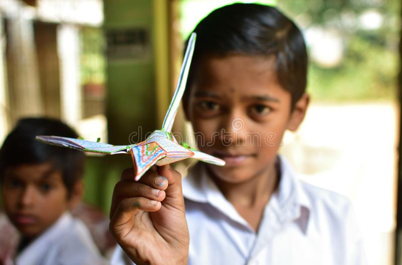 A primary school student showing a aeroplane made by paper in the craft class at a rural primary school in West Bengal, India. Jhargram, India - December 13 royalty free stock photo