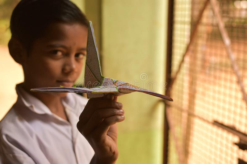 A primary school student showing a aeroplane made by paper in the craft class at a rural primary school in West Bengal, India. Jhargram, India - December 13 stock image