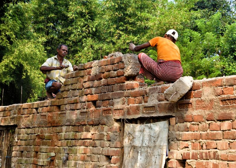 Jhargram, India- November : Indian men handyman breaks a brick wall with a hammer, builds and repairs his house. Jhargram, India- November 22, 2019: Indian men royalty free stock photo