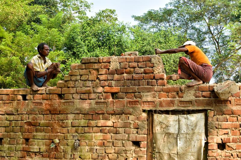 Jhargram, India- November : Indian men handyman breaks a brick wall with a hammer, builds and repairs his house. Jhargram, India- November 22, 2019: Indian men stock photography
