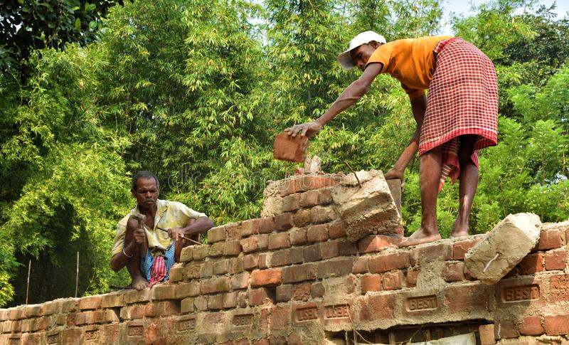 Jhargram, India- November : Indian men handyman breaks a brick wall with a hammer, builds and repairs his house. Jhargram, India- November 22, 2019: Indian men royalty free stock image