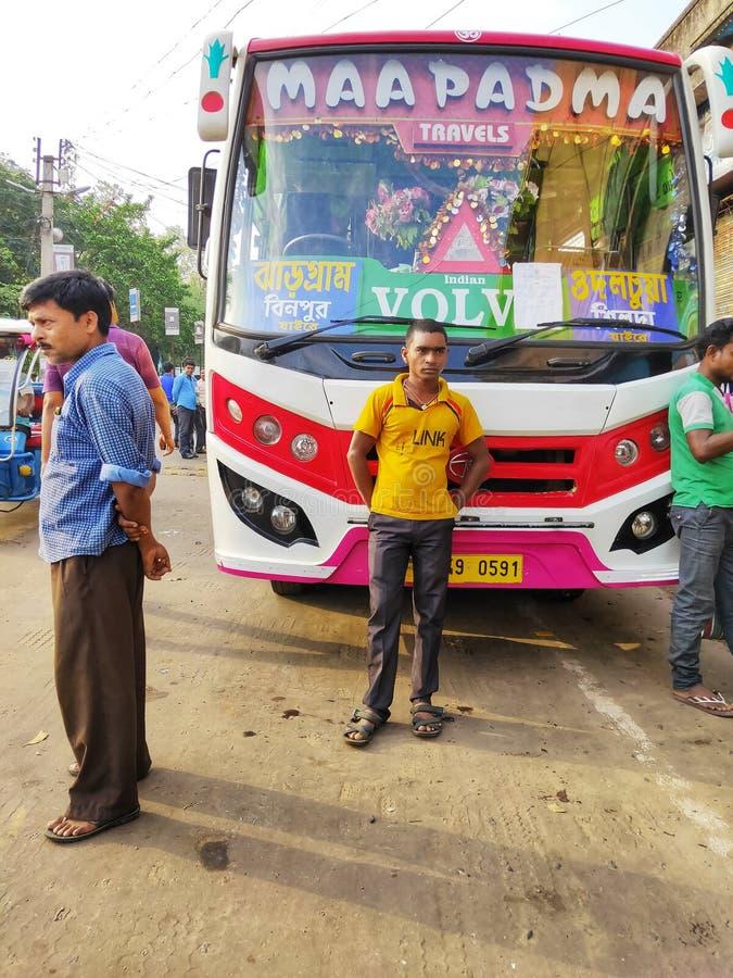 Jhargram västra Bengal, Indien - Maj 05, 2018: Folket väntar på bussen på den Jhargram hållplatsen en buss väntade också på arkivfoton