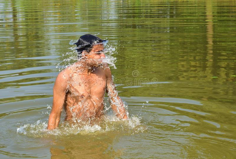 A young man swimming in the pond on a summer noon . Summer swimming. playing with water in summer season. Jhargram, West Bengal, India - november 23, 2018: A stock images