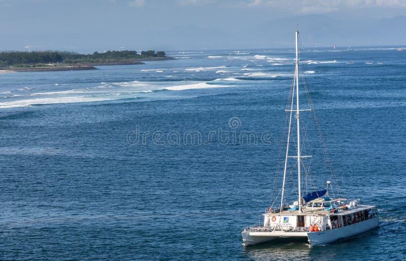 Ji Pantai Serangan strand och att segla fartyget utanför den Benoa hamnen i Bali, Indonesien royaltyfri fotografi