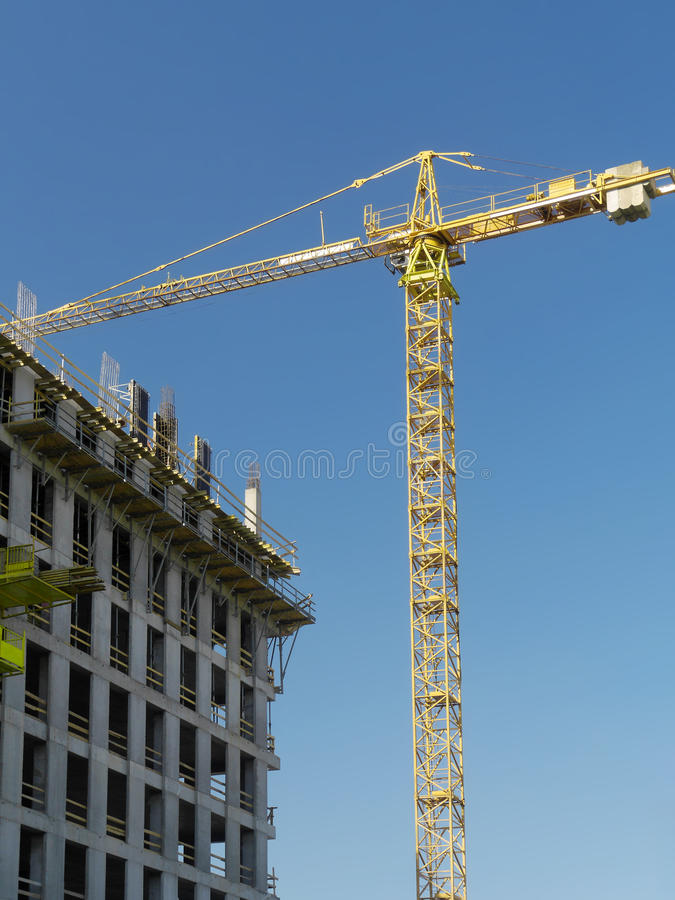 Jib crane. Highrise building under construction and jib crane over clear blue sky stock image