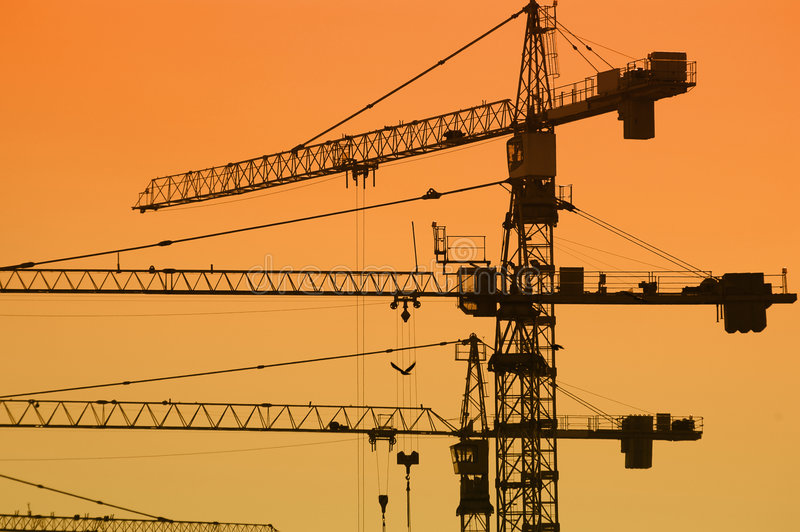 Jib cranes. Jib crane silhouettes against sunset sky royalty free stock images