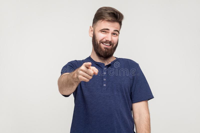 Jibe, bad taunt concept. Young adult man pointing finger. And toothy smile. Studio shot, gray background royalty free stock images