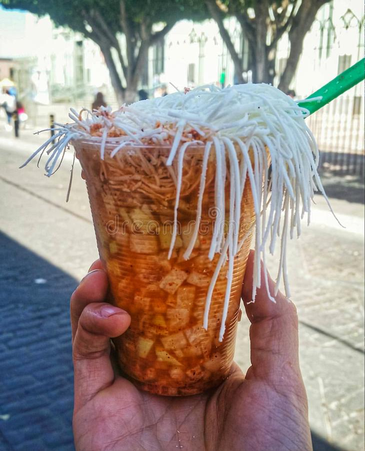 Jicama in a cup called bomba that contains chilli powder, lime, cheese, onion and vinegar and is a traditional street food in the. Jicama in a cup called bomba stock photo