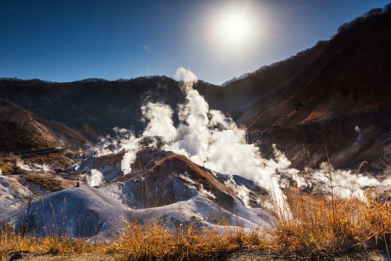 Jigokudani hell valley at sunrise, Noboribetsu. Jigokudani hell valley with dense steam sulfur gas against sunrise and blue sky, Hokkaido, Japan. Travel stock photo