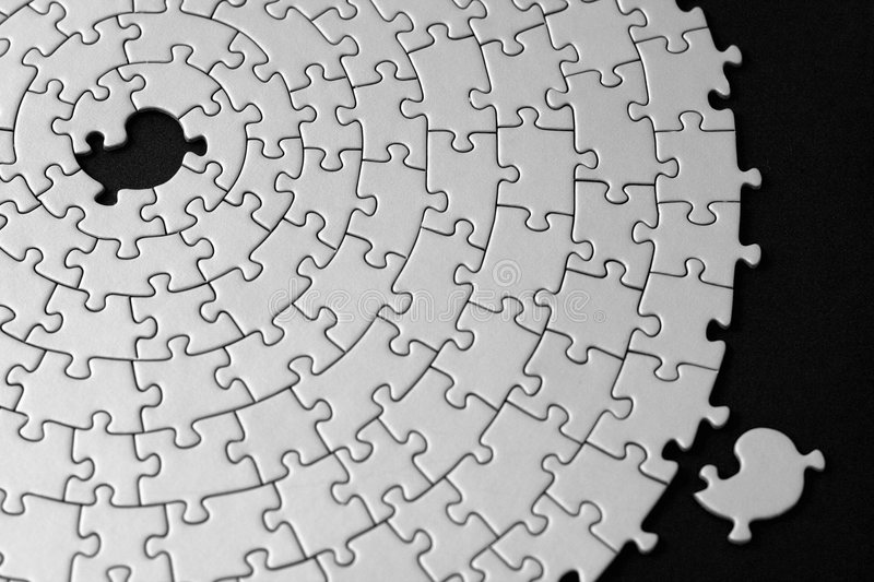 Jigsaw in black and white with one missing piece laying aside. Shallow DOF, focus is on the hole - adobe RGB royalty free stock photography