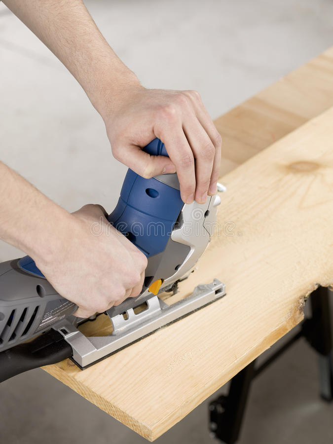 Jigsaw and cutting a piece of wood royalty free stock photos