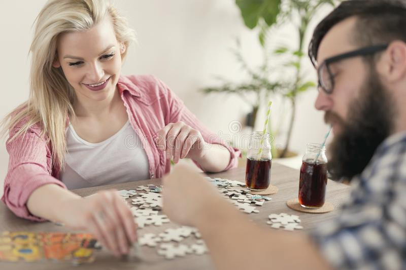Jigsaw puzzle. Couple in love sitting on the floor next to a table, solving a jigsaw puzzle problem and enjoying their leisure time activities stock photo