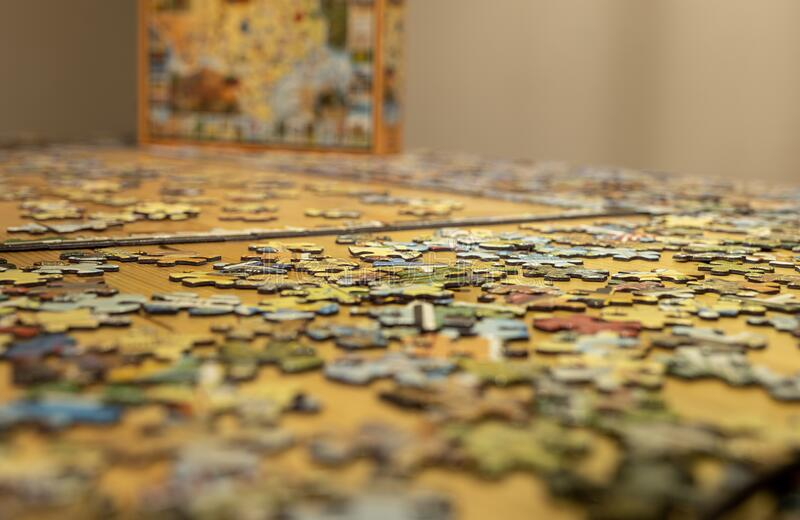 Jigsaw puzzle pieces on a table with shallow focus stock image