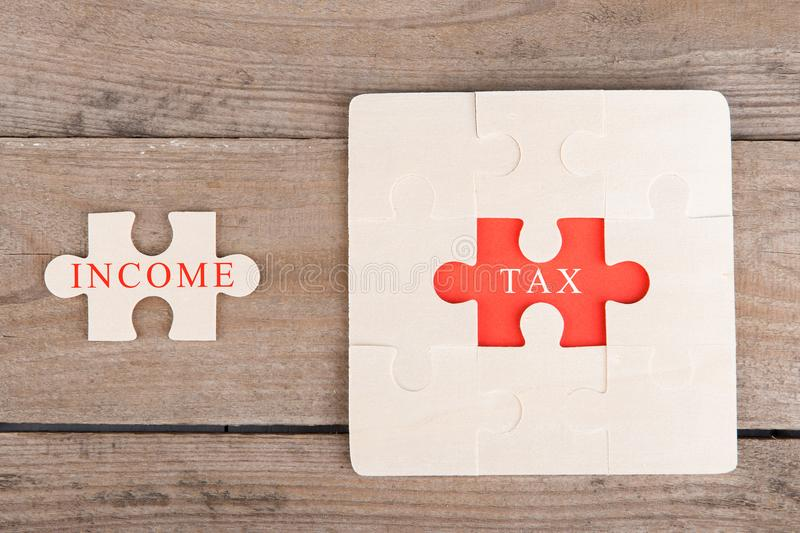 Jigsaw Puzzle Pieces with words & x22;Tax& x22; and & x22;Income& x22; royalty free stock image