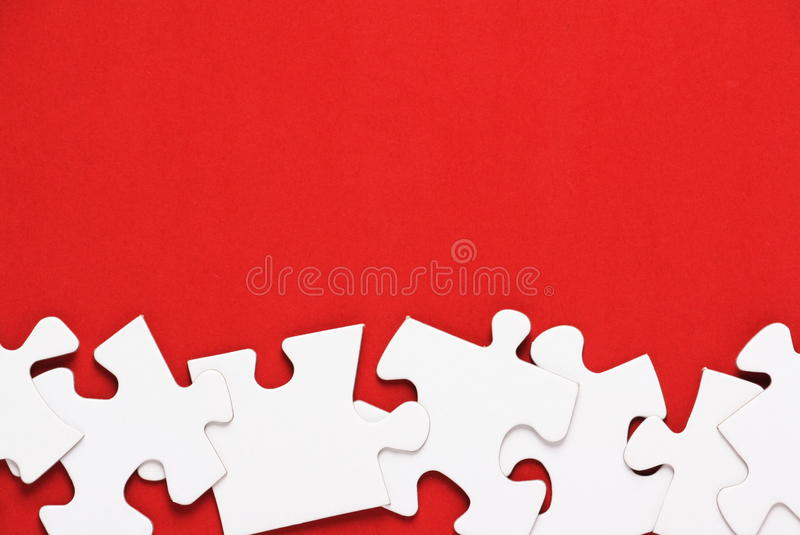 Jigsaw Puzzle on Red. Blank Jigsaw Puzzle pieces on a bright red background stock photos