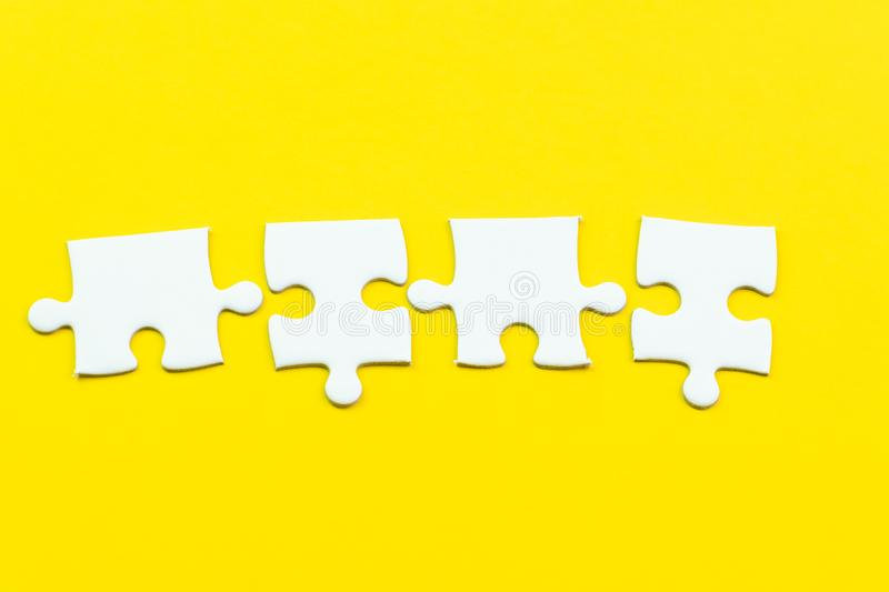 4 jigsaw puzzle on solid yellow background using as 4 important thing combine or working together to success or solve problem stock photos
