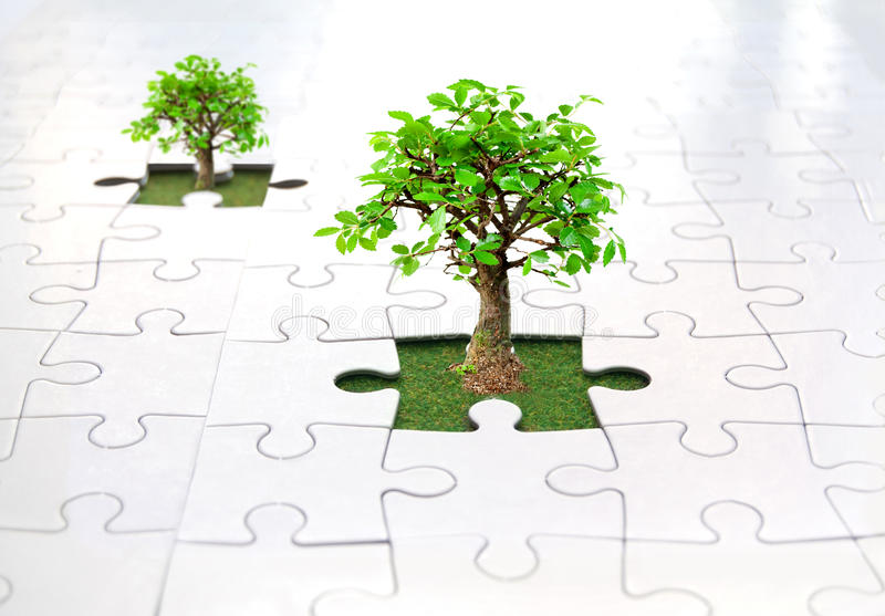 Jigsaw puzzle tree. Small trees growing from grass inside a jigsaw stock images