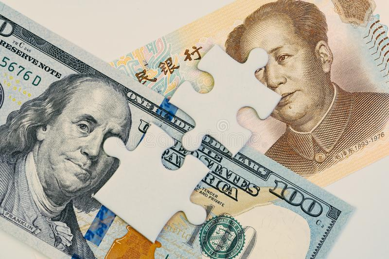 2 jigsaw puzzle on US America Dollar and Chinese Yuan banknotes using as tariff or trade war negotiation or future direction royalty free stock photos