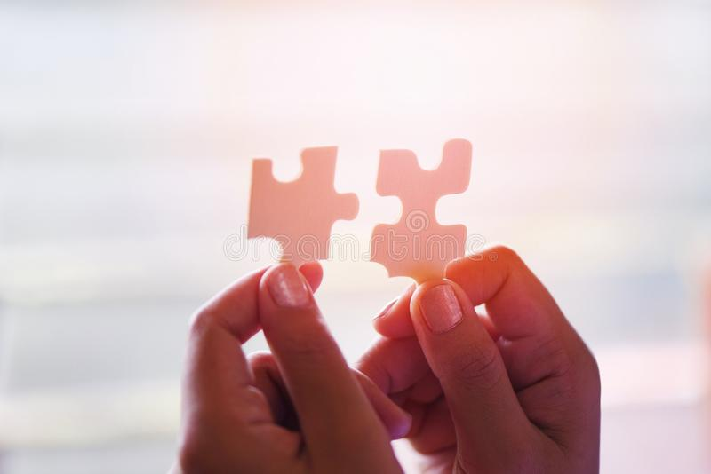Jigsaw puzzle with woman hand connecting jigsaw piece with sunlight / Business solutions partnership success and strategy. Concep stock images