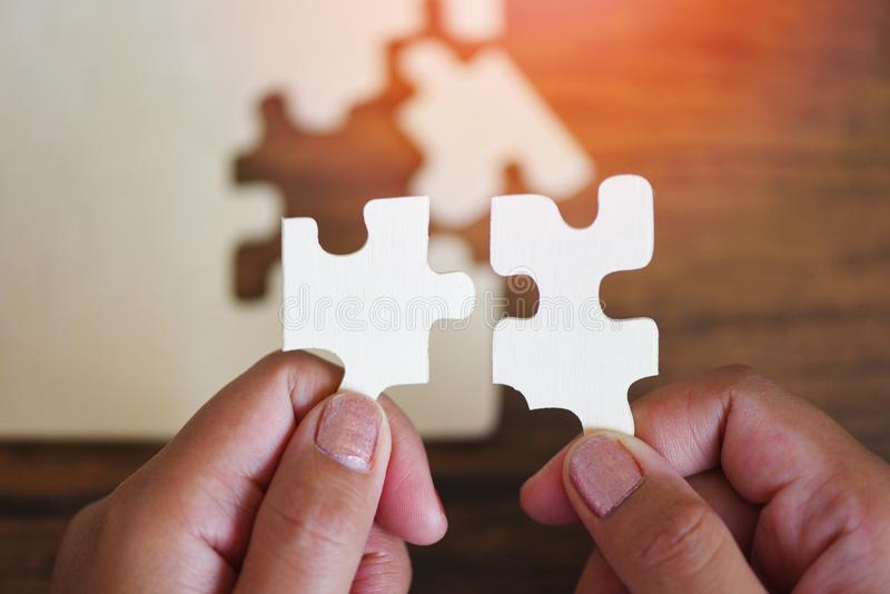 Jigsaw puzzle with woman hand connecting jigsaw piece with sunlight - Business solutions partnership success and strategy concept. Jigsaw puzzle with woman hand stock images