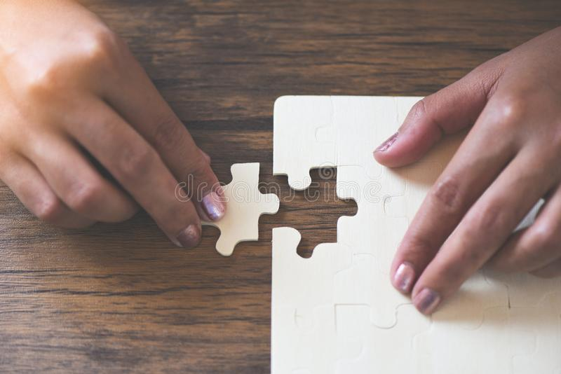 Jigsaw puzzle with woman hand connecting jigsaw piece on wooden background / Business solutions partnership success and strategy stock photography