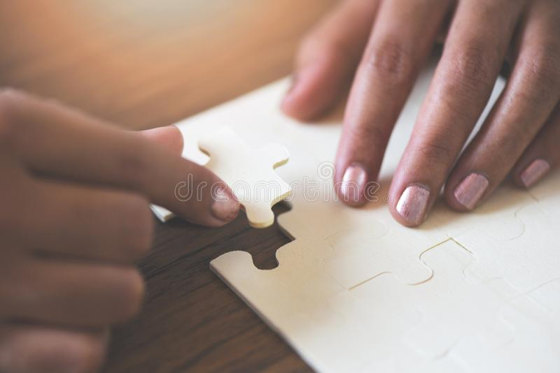 Jigsaw puzzle with woman hand connecting jigsaw piece on wooden background / Business solutions partnership success and strategy. Concept royalty free stock images