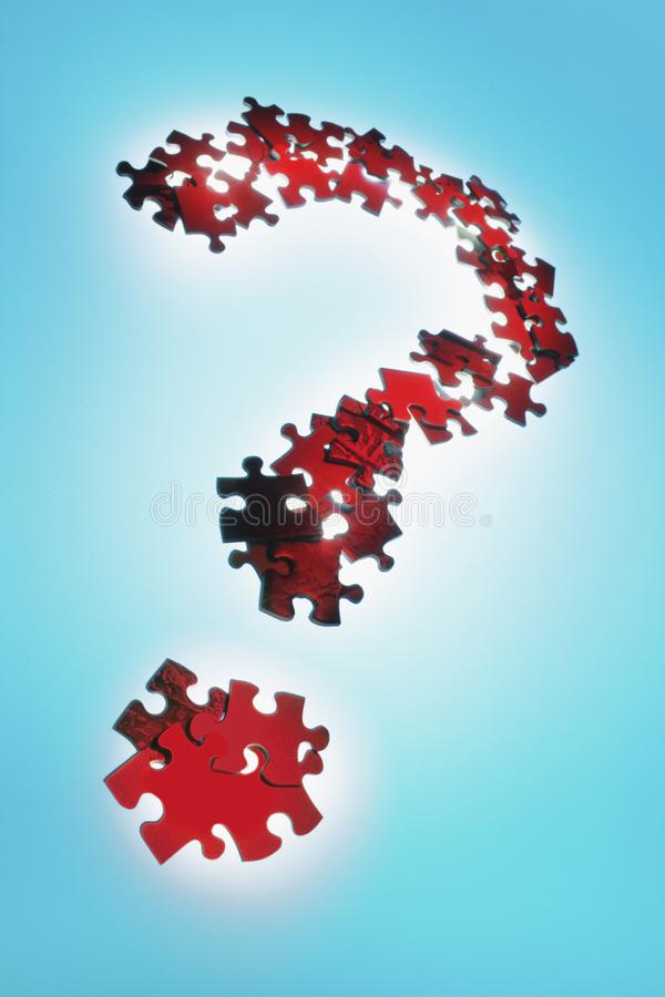 Jigsaw Puzzles Arranged in Question Mark Sign. On Blue Background royalty free stock photo